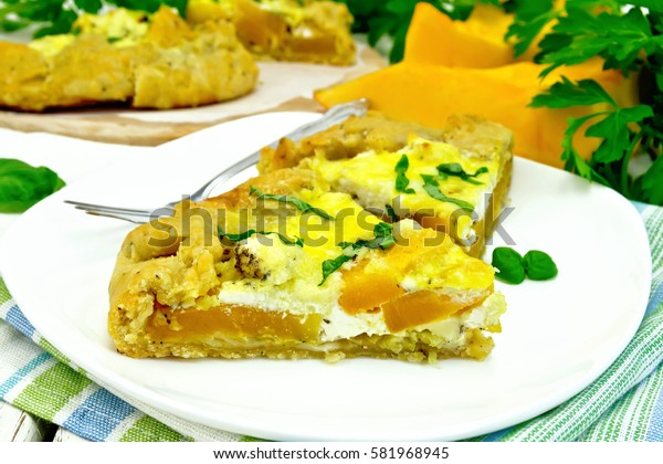 Two piece of the pie of pumpkin, salty feta cheese, eggs, cream and herbs in a plate on a napkin, basil on the background light wooden boards