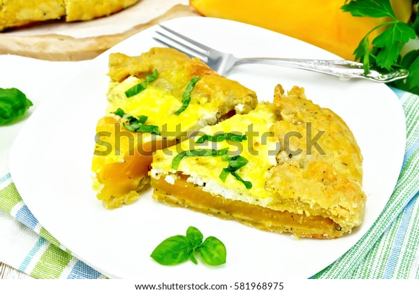 Two piece of the pie of pumpkin, salty feta cheese, eggs, cream and herbs in a plate on towel, basil on the background light wooden boards