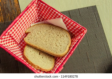 two pieces of bread in a beautiful breadbox on a table in a cafe. Fresh cut bread on white paper in bread box on wooden table with background