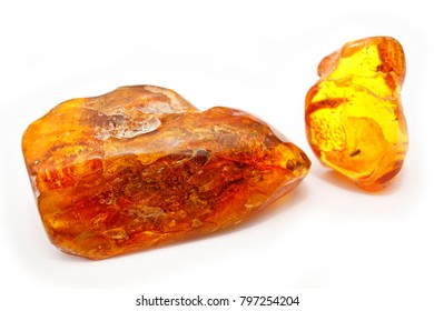 Two pieces of bright amber of different transparency red and yellow on a white background. Crystals of amber as a natural mineral for making jewelry. Sunstone. Macro photo  of amber with Inclusions