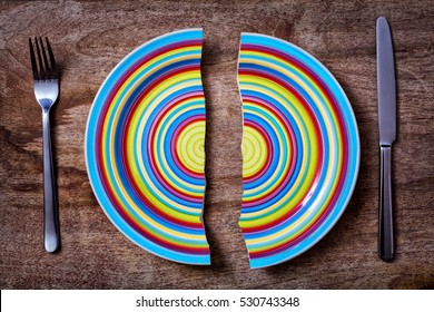 two pieces of broken colorful plate with fork and knife on wooden background; symbol of separation or divorce
