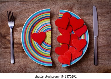 two pieces of broken colorful plate with one red heart on left side and many hearts on the right side on wooden background; symbol of unbalanced feelings, separation, divorce