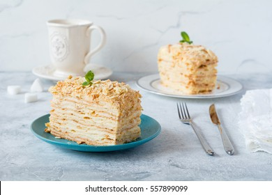 Two pieces of cake Napoleon on blue plate on pink textile. Russian cuisine, multi layered cake with pastry cream, close up view