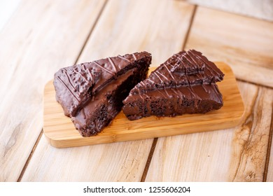 Two pieces of chocolate cake on a wooden stand. All on a wooden background.