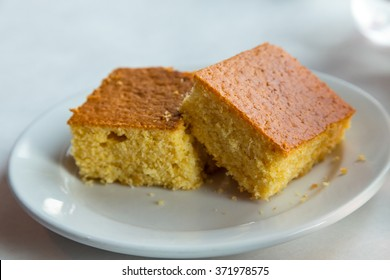 Two pieces of cornbread on a white plate