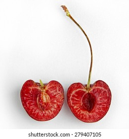Two pieces of cut cherry isolated on white background. Half of ripe, juicy and delicious cherry.