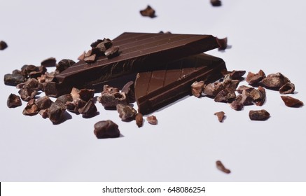 Two pieces of dark chocolate with chopped  cocoa beans on white background