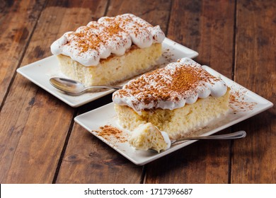 Two pieces of a delicious three milk cake dessert on a wooden background