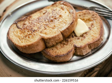 Two pieces of French toast with butter on a silver plate and wooden board.
