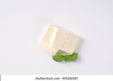 two pieces of fresh feta cheese with basil on white background