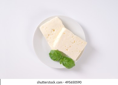 two pieces of fresh feta cheese with basil on white plate