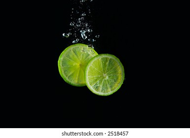 two pieces of fresh juicy lime making bubbles in water