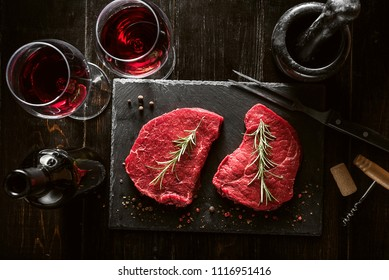 two pieces of fresh meat prepared for frying and wine with glasses on a wooden table