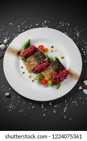 Two pieces of fried fish on white plate