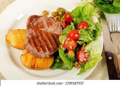 two pieces of grilled potato and grilled meat next to lettuce with tomatoes and olives on a white plate