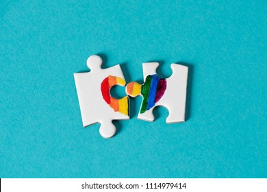 two pieces of a puzzle, made by myself, which put together form a rainbow heart, on a blue background, depicting the lack of right of same-sex marriage or the divorce of same-sex couples