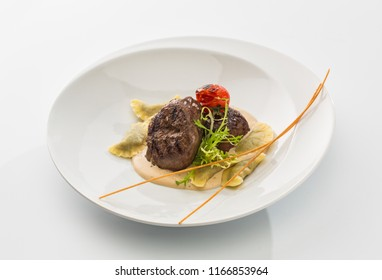two pieces of roasted meat with sauce and ravioli on a plate isolated on white background