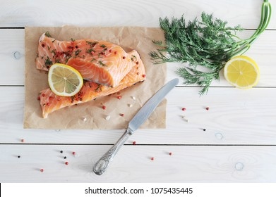 Two pieces of salmon of weak salt on kraft paper. There is a bunch of greenery, half a lemon and a knife. Light wooden background. View from above. Close-up.