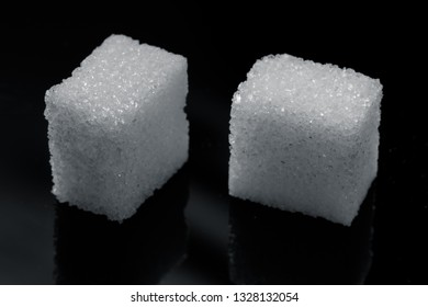 two pieces of sugar cubes on a black background