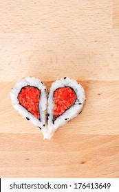 Two pieces of sushi forming the heart shape on wooden cutting board
