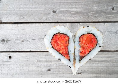 Two pieces of sushi forming the heart shape on a gray wooden background