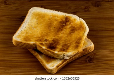 Two pieces of toasted white bread on a wooden surface