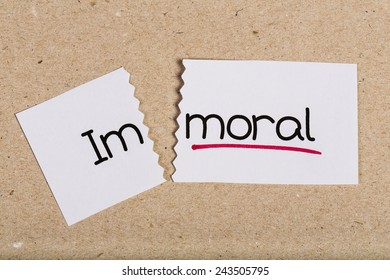 Two pieces of white paper with the word immoral turned into moral