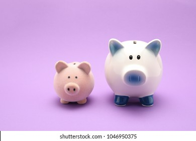 two piggy bank together one small another big isolated purple color background