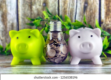 Two piggy banks and coins inside the light bulb. Green eco energy concept. Electricity prices, energy saving.