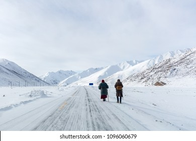 two pilgrims on snow area plateau in tibet