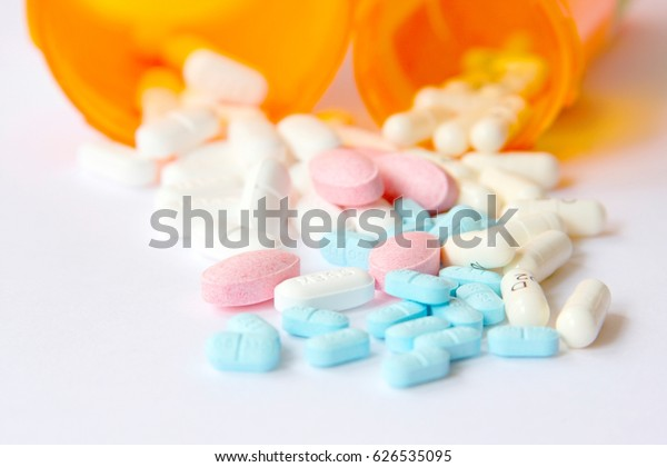 Two pill bottles spilling out pink, blue and white pills. Isolated on white. Selective focus.