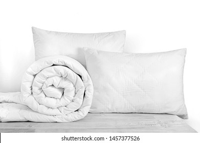 Two pillows and rolled duvet isolated on white. Bedding objects isolated against white background. Bedding items catalog