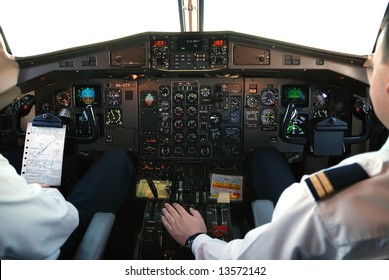 two pilots in cockpit of plane during mountain-flight