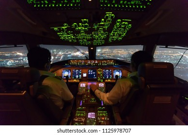 Two pilots are flying the airplane in approach phase to the runway in night time while raining. Cityscape and airport are seen outside cockpit. Pilots and airplane instruments are inside cockpit.
