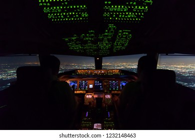 Two pilots are flying the airplane in final approach phase to the runway in night time. Cityscape and airport are seen outside cockpit. Pilots and airplane instruments are inside cockpit.