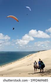 Deux pilotes marchant sur le sable regardent les parapentistes voler sur la dune de Pyla. Le ciel d'été est bleu avec quelques nuages