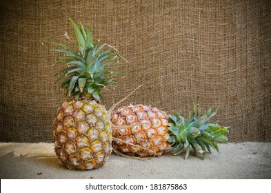 two pine apples on brownish sack stock photo