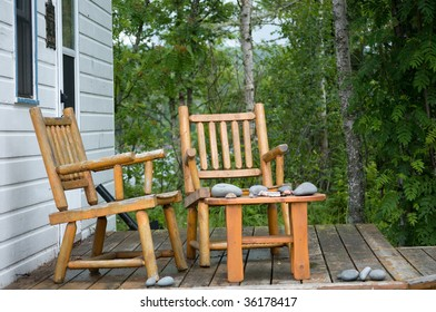 two pine log chairs on porch with stacks of gathered rocks