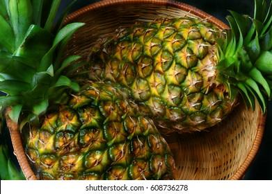 two pineapples in a wicker basket