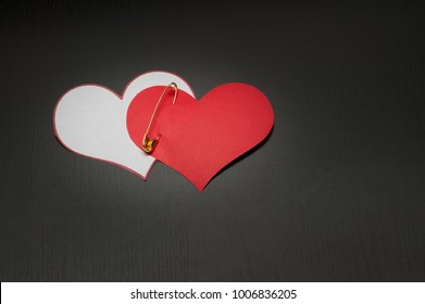 two pined paper  white and red hearts on dark wood background