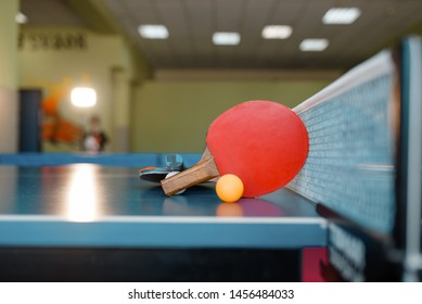 Two ping pong rackets and ball on table with net
