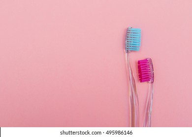 two pink and blue toothbrushes on pink background