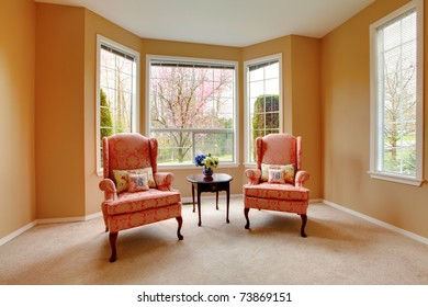 Two pink chairs in the living room with cherry blossom