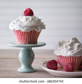 Two pink cupcakes with with frosting and raspberry garnish.