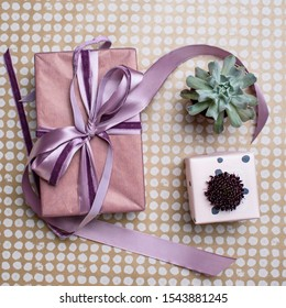 Two pink gift box with scabiosa flower and succulent on craft paper