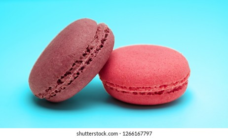Two pink macaroons on a light blue background.
