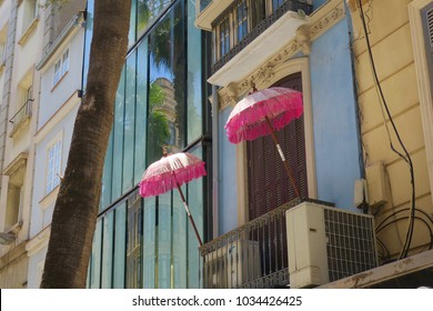 two pink parasols on a balcony in Malaga