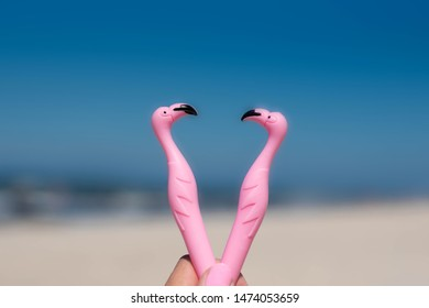 Two pink rubber flamingos against the blue sky, sea and sand. Valentine's day card. Love, vacation , travel concept. Selective focus.
