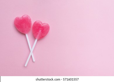 two Pink Valentine's day heart shape lollipop candy on empty pastel pink paper background. Love Concept. top view. Minimalism colorful hipster style.