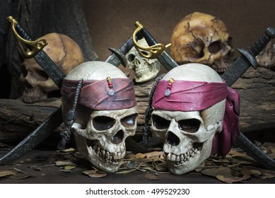 Two pirate skull with two swords over three human skull in the forest still life style